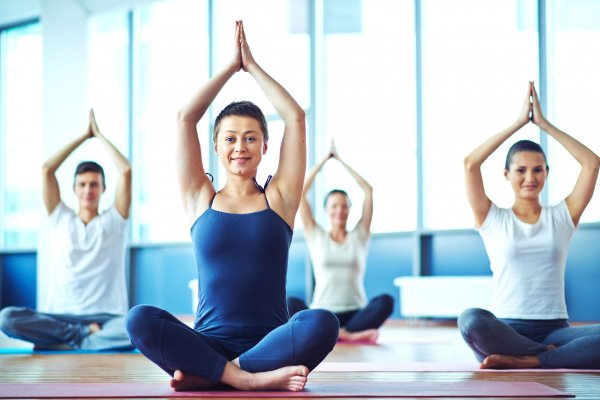 53428284 - young woman practicing yoga in yoga class in fitness center