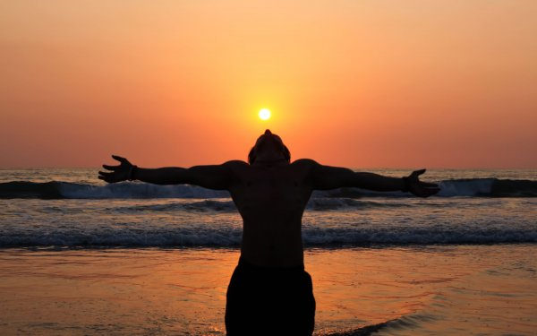 14961662 - a young man stands as a living shadow in front of the ocean with his arms outstreatched to the orange sky and his head tilted back to absorb the setting sun