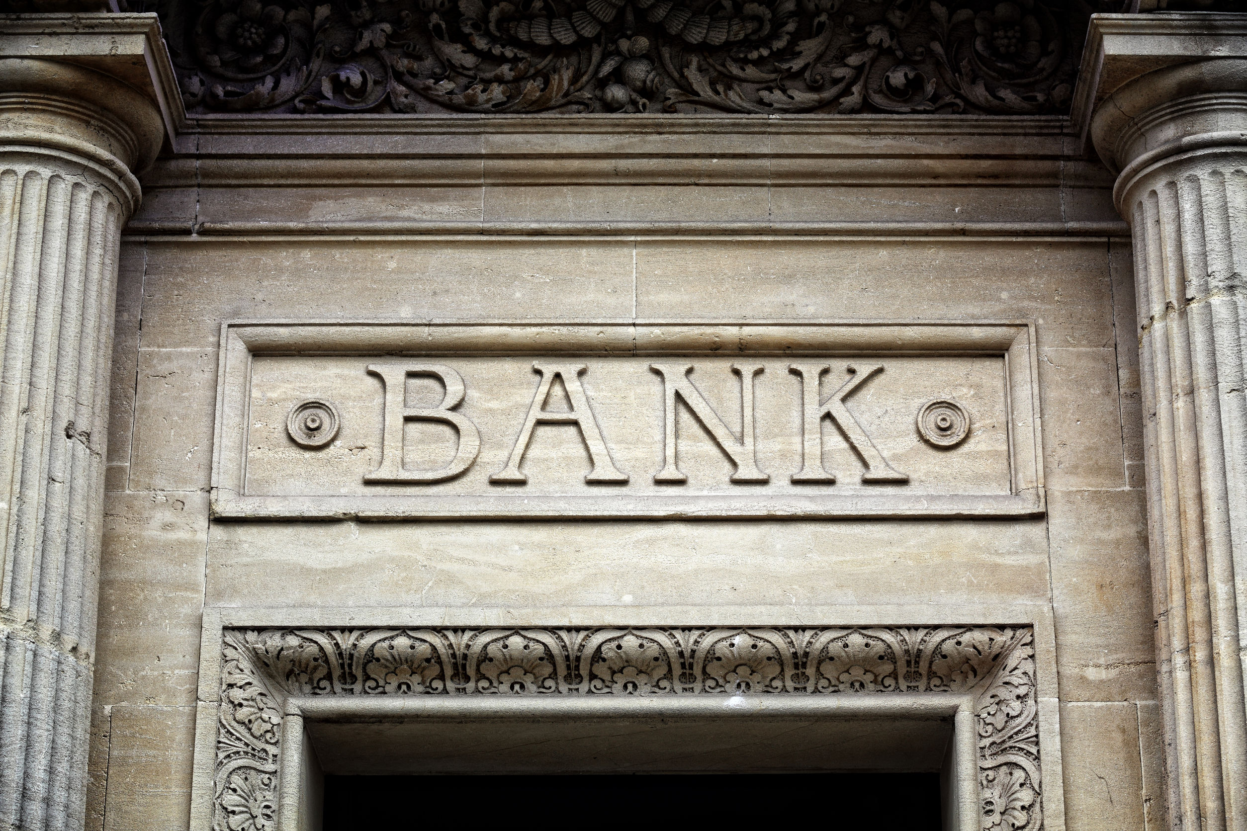 41818583 - old bank sign engraved in stone or concrete above the door of financial building concept for finance and business