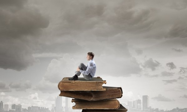48390614 - young businessman sitting alone on pile of old books