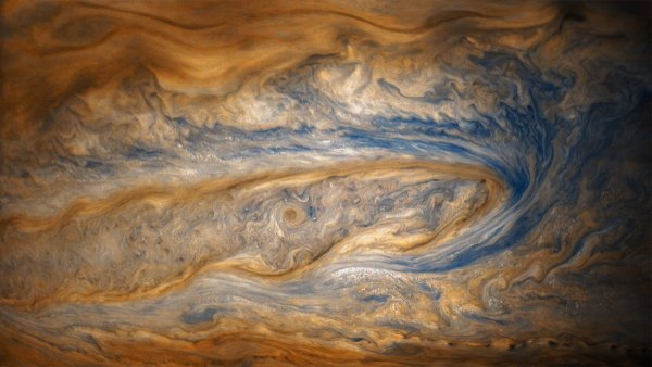 in this older view of jupiter from junos eighth perijove two cloud bands battle for dominance one of which contains a swirling storm many times larger than a hurricane on earth