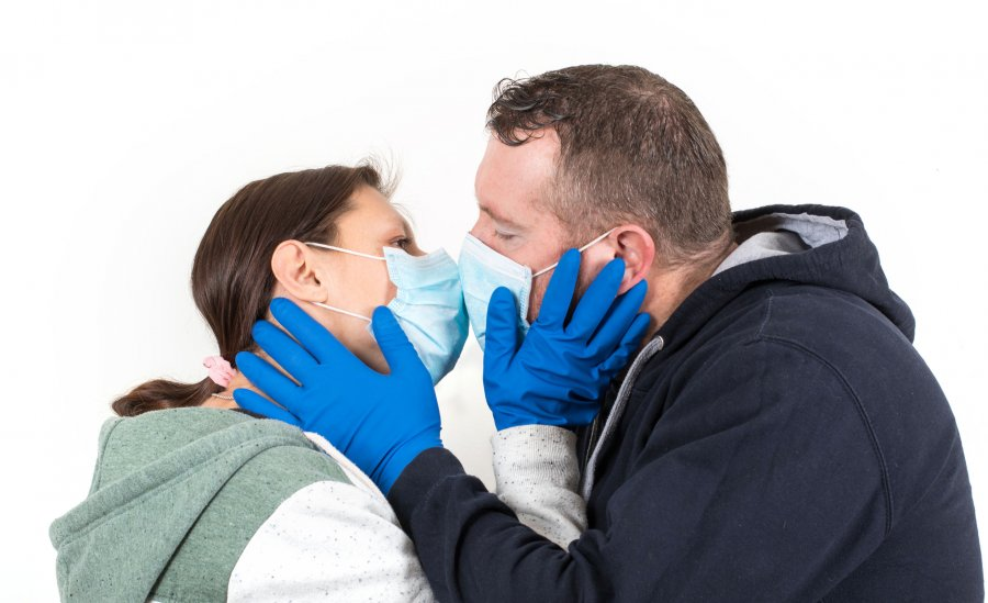 Couple wearing a virus face mask kissing concept for corona viru