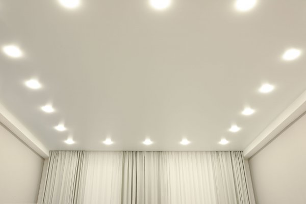 White stretch ceiling with spot lights in room